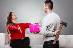 Hombre de Insincire que sostiene el hacha que da la caja de regalo a la mujer Fotos de archivo