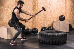 Hombre de la aptitud del deporte que golpea el neumático con el entrenamiento de Crossfit del trineo del martillo, individuo sano imagen de archivo libre de regalías