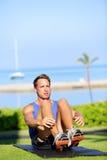 Hombre de la aptitud del entrenamiento que hace el ejercicio de sentar-UPS Foto de archivo