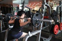 Hombre de la aptitud en el gimnasio que hace posición en cuclillas Hombre con el gimnasio del equipo de entrenamiento del peso de Imagenes de archivo
