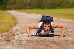 Hombre de la aptitud que ejercita los pectorales, al aire libre Cruz-entrenamiento masculino muscular afuera Foto de archivo
