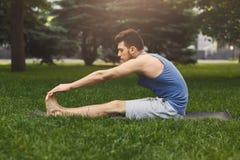 Hombre de la aptitud que estira en hierba al aire libre Imagen de archivo libre de regalías