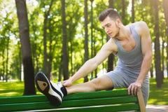 Hombre de la aptitud que estira las piernas al aire libre Imagenes de archivo