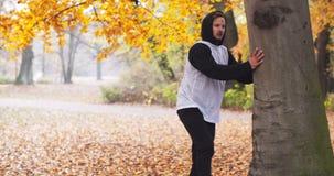 Hombre de la aptitud que hace estirando los ejercicios al aire libre Entrenamiento de la aptitud del hombre joven al aire libre almacen de video