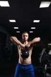 Hombre de la aptitud que hace un entrenamiento del peso levantando el kettlebell pesado fotografía de archivo libre de regalías
