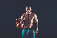 Hombre de la aptitud que hace un entrenamiento del peso levantando el kettlebell pesado foto de archivo