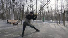 Hombre de la aptitud que usa el equipo del lazo del trx para entrenar en la tierra de deporte al aire libre metrajes
