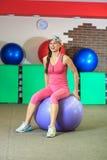 Hombre de la aptitud training La muchacha blanca hermosa joven en un traje rosado de los deportes hace ejercicios físicos con una Fotografía de archivo libre de regalías