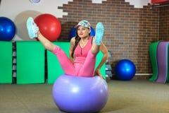 Hombre de la aptitud training La muchacha blanca hermosa joven en un traje rosado de los deportes hace ejercicios físicos con una Fotografía de archivo