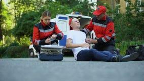 Hombre de la ayuda del equipo de la ambulancia que sufre de dolor en pecho, problemas del corazón o asma almacen de video