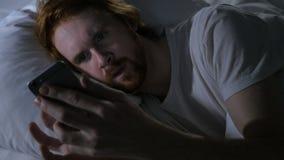 Hombre de la barba del pelirrojo en Smartphone que hojea en la noche en cama metrajes