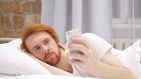 Hombre de la barba del pelirrojo que miente en cama y que hojea en Smartphone en la noche almacen de video