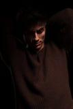 Hombre de la belleza con los codos para arriba que miran abajo Imagen de archivo