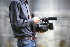Hombre de la cámara de vídeo con la cámara foto de archivo