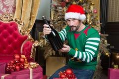 Hombre de la calma que le mira mientras que sostiene la botella grande de alcohol fotos de archivo libres de regalías
