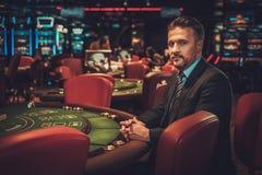 Hombre de la clase alta detrás de la tabla de juego en un casino imagen de archivo
