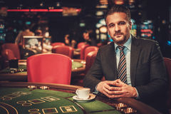 Hombre de la clase alta detrás de la tabla de juego en un casino imagen de archivo libre de regalías