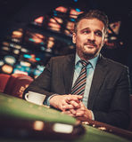 Hombre de la clase alta detrás de la tabla de juego en un casino imagenes de archivo