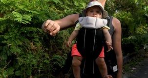 Hombre de la cosecha con el bebé en portador almacen de metraje de vídeo