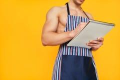 Hombre de la cosecha en la escritura del delantal en libreta imágenes de archivo libres de regalías