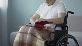 Hombre de la edad avanzada con las incapacidades que revisan el álbum con las fotos, parientes que falta almacen de video