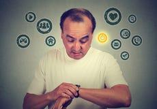 Hombre de la Edad Media que usa comprobando tiempo en su reloj elegante con los iconos de los apps Concepto del artilugio de la n Fotos de archivo