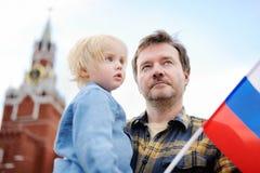 Hombre de la Edad Media y su pequeño hijo con la bandera rusa con la torre Rusia, Moscú de Spasskaya en fondo Imagen de archivo libre de regalías
