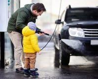 Hombre de la Edad Media y su pequeño hijo que lavan un coche en un carwash Imagenes de archivo