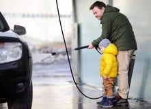Hombre de la Edad Media y su pequeño hijo que lavan un coche en un carwash Imagen de archivo