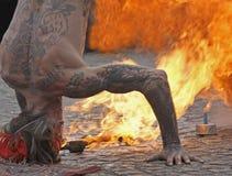 Hombre de la expectoración del fuego en headstand Fotos de archivo libres de regalías