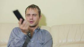 Hombre de la felicidad con la TV de observación teledirigida en casa almacen de metraje de vídeo