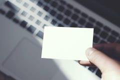 Hombre de la imagen del primer que muestra la tarjeta de visita blanca en blanco y que usa el fondo borroso ordenador portátil mo Fotos de archivo libres de regalías