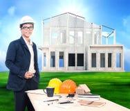 Hombre de la ingeniería con la tabla de funcionamiento y proyecto casero sobre hermoso Fotos de archivo libres de regalías