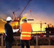 Hombre de la ingeniería que trabaja en sitio de la construcción de edificios con el worke Foto de archivo libre de regalías