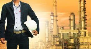 Hombre de la ingeniería y casco de seguridad que se opone a refinería de petróleo imagen de archivo
