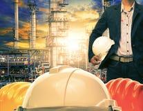 Hombre de la ingeniería y casco de seguridad contra industrie de la refinería de petróleo Foto de archivo libre de regalías