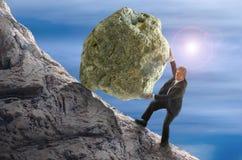 Hombre de la metáfora de Sisyphus que rueda la bola enorme de la roca encima de la colina Fotos de archivo libres de regalías