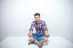 Hombre de la moda de los jóvenes que descansa sobre una tabla blanca Foto de archivo