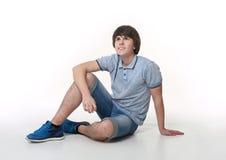 Hombre de la moda de los jóvenes que presenta en pantalones cortos de los vaqueros y zapatos azules de las zapatillas de deporte Fotografía de archivo libre de regalías