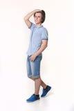 Hombre de la moda de los jóvenes que presenta en pantalones cortos de los vaqueros y zapatos azules de las zapatillas de deporte Foto de archivo