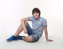 Hombre de la moda de los jóvenes que presenta en pantalones cortos de los vaqueros y zapatos azules de las zapatillas de deporte Fotos de archivo libres de regalías