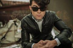 Hombre de la moda de los jóvenes que se sienta cerca de fábrica vieja Fotos de archivo