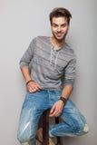 Hombre de la moda de los jóvenes que se sienta en un taburete, sonriendo Imágenes de archivo libres de regalías