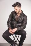 Hombre de la moda de los jóvenes que se sienta en una silla mientras que mira abajo Foto de archivo