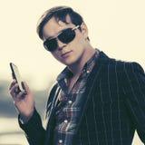 Hombre de la moda de los jóvenes en gafas de sol usando el teléfono elegante al aire libre Imagenes de archivo