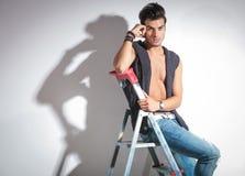 Hombre de la moda que descansa sobre una escalera Foto de archivo libre de regalías