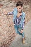 Hombre de la moda que se inclina en una pared de ladrillo Imágenes de archivo libres de regalías