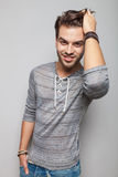 Hombre de la moda que sonríe y que fija su pelo Fotografía de archivo