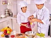Hombre de la mujer en sombrero del cocinero que cocina el pollo Foto de archivo