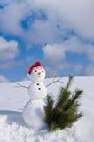 Hombre de la nieve en el casquillo de santa Foto de archivo libre de regalías